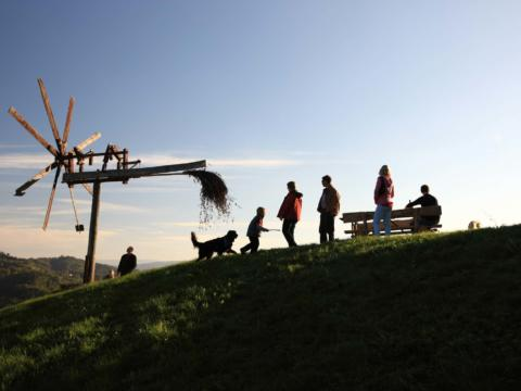 Landschaft mit Klapotetz in Sulmtal-Sausal mit einer Gruppe von Menschen, die die wunderschöne Abendstimmung genießt. JUFA Hotels bietet Ihnen den Ort für erlebnisreichen Natururlaub für die ganze Familie.