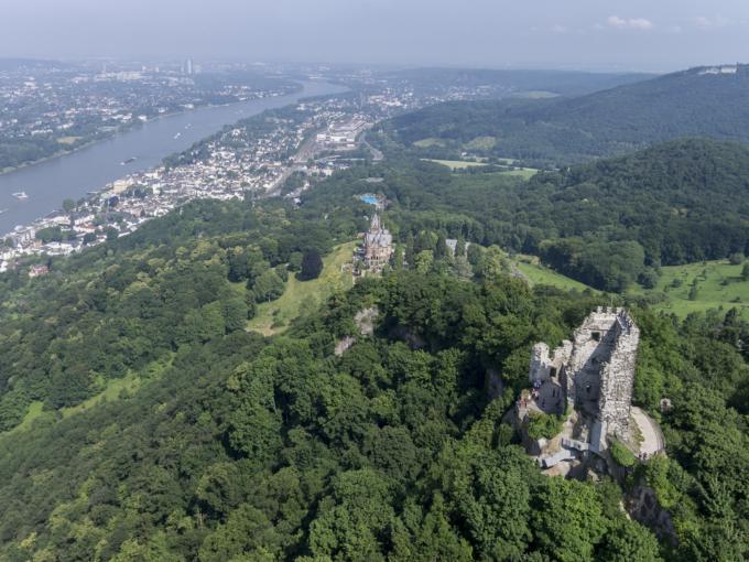 Eine Luftaufnahme des Drachenfels mit Blick auf die Burgruine Drachenfels, den Rhein und Königswinter.JUFA Hotels bietet erlebnisreiche Städtetrips für die ganze Familie und den idealen Platz für Ihr Seminar.