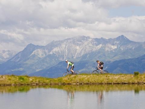 Ein Paar beim Mountainbiken neben einem Bergsee in der Ferienregion Lungau. JUFA Hotels bietet Ihnen den Ort für erlebnisreichen Natururlaub für die ganze Familie.