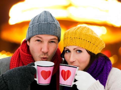 Ein Paar mit Hauben trinkt aus Herztassen Gülühwein auf einem Adventmarkt. JUFA Hotels bietet erholsamen Familienurlaub und einen unvergesslichen Winterurlaub.