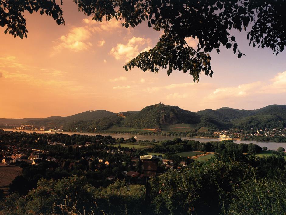 Eine Panoramaaufnahme des Siebengebirges mit Rhein im Vordergrund bei Sonnenuntergang. JUFA Hotels bietet erlebnisreiche Städtetrips für die ganze Familie und den idealen Platz für Ihr Seminar.