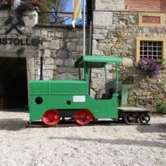 Schaubergwerk Knappenberg mit grüner Lokomotive vor Erbstollen-Eingang. JUFA Hotels bieten erholsamen Familienurlaub und einen unvergesslichen Winter- und Wanderurlaub.