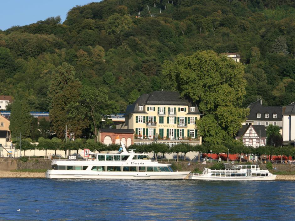 Ein Schiff an einer Anlegestelle vor Rheinfront in Königswinter im Sommer. JUFA Hotels bietet erlebnisreiche Städtetrips für die ganze Familie und den idealen Platz für Ihr Seminar.