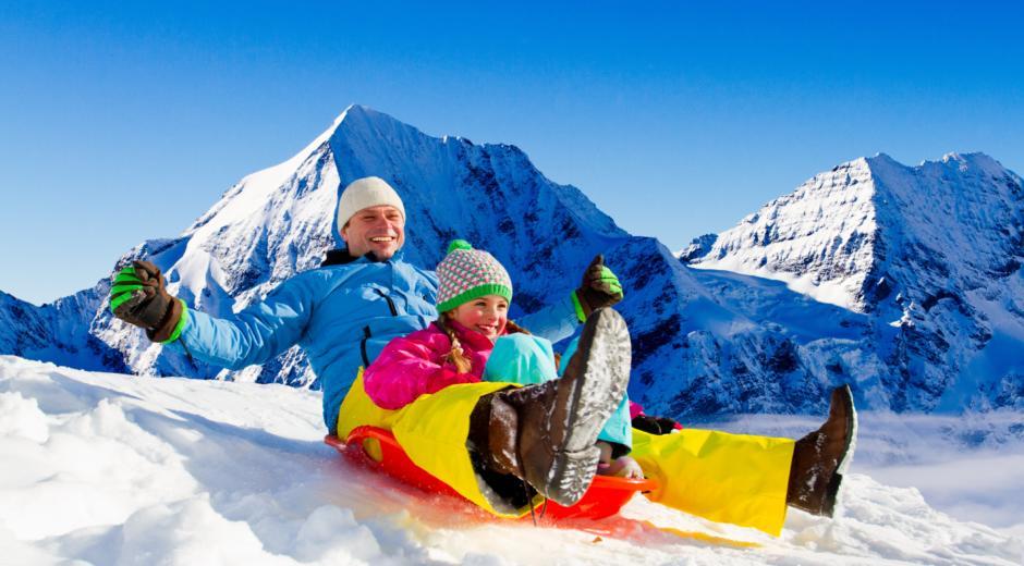 Sie sehen einen Vater mit seiner Tochter auf einem roten Bob beim Schlittenfahren mit schneebedeckten Bergern im Hintergrund. JUFA Hotels bietet erholsamen Familienurlaub und einen unvergesslichen Winterurlaub.