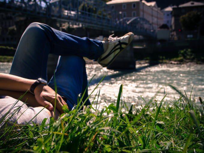 Person liegt am Ufer der Salzach und blickt auf die Altstadt
