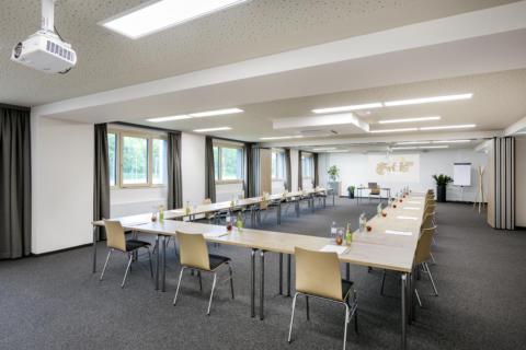 Sie sehen eine Ansicht des Seminarraums mit Beamer im JUFA Hotel Weiz. Der Ort für erfolgreiche und kreative Seminare in abwechslungsreichen Regionen.