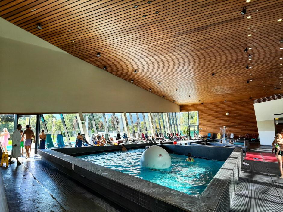 Sie sehen ein Schwimmbecken und die wunderschöne Holzdeckein der Aqualux Therme. JUFA Hotels bietet tollen Urlaub mit viel Abenteuer und Spaß für die ganze Familie.