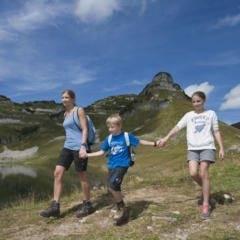 Sie sehen eine Mutter mit Kindern beim Wandern am Augstsee auf dem Loser im Sommer. JUFA Hotels bietet Ihnen den Ort für erlebnisreichen Natururlaub für die ganze Familie.