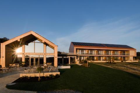 Sie sehen eine Außenansicht vom EventArium am JUFA Hotel Neutal – Landerlebnis mit Sonnenstrahlen. JUFA Hotels bietet Ihnen den Ort für erlebnisreichen Natururlaub für die ganze Familie.