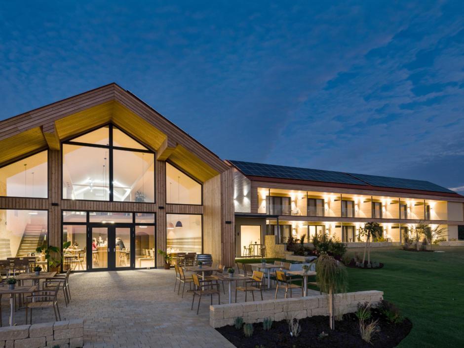 Sie sehen eine Außenansicht vom EventArium am JUFA Hotel Neutal – Landerlebnis mit Terrasse am Abend. JUFA Hotels bietet Ihnen den Ort für erlebnisreichen Natururlaub für die ganze Familie.