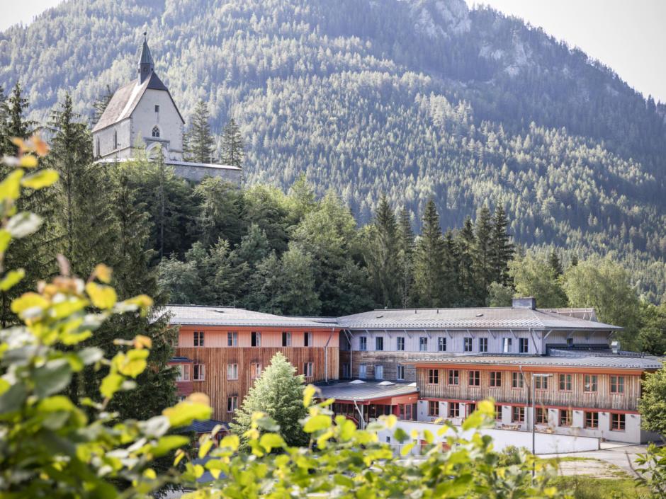 Sie sehen das JUFA Hotel Sigmundsberg von außen und im Hintergrund eine Kirche. Der Ort für erholsamen Familienurlaub und einen unvergesslichen Winter- und Wanderurlaub.