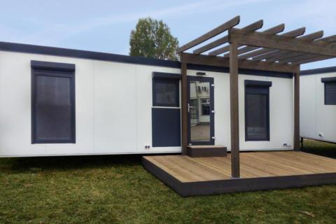 Sie sehen eine Außenansicht von einem Mobile Home am JUFA Vulkan Thermen-Resort mit einer Terrasse. JUFA Hotels bietet erholsamen Thermenspass für die ganze Familie.