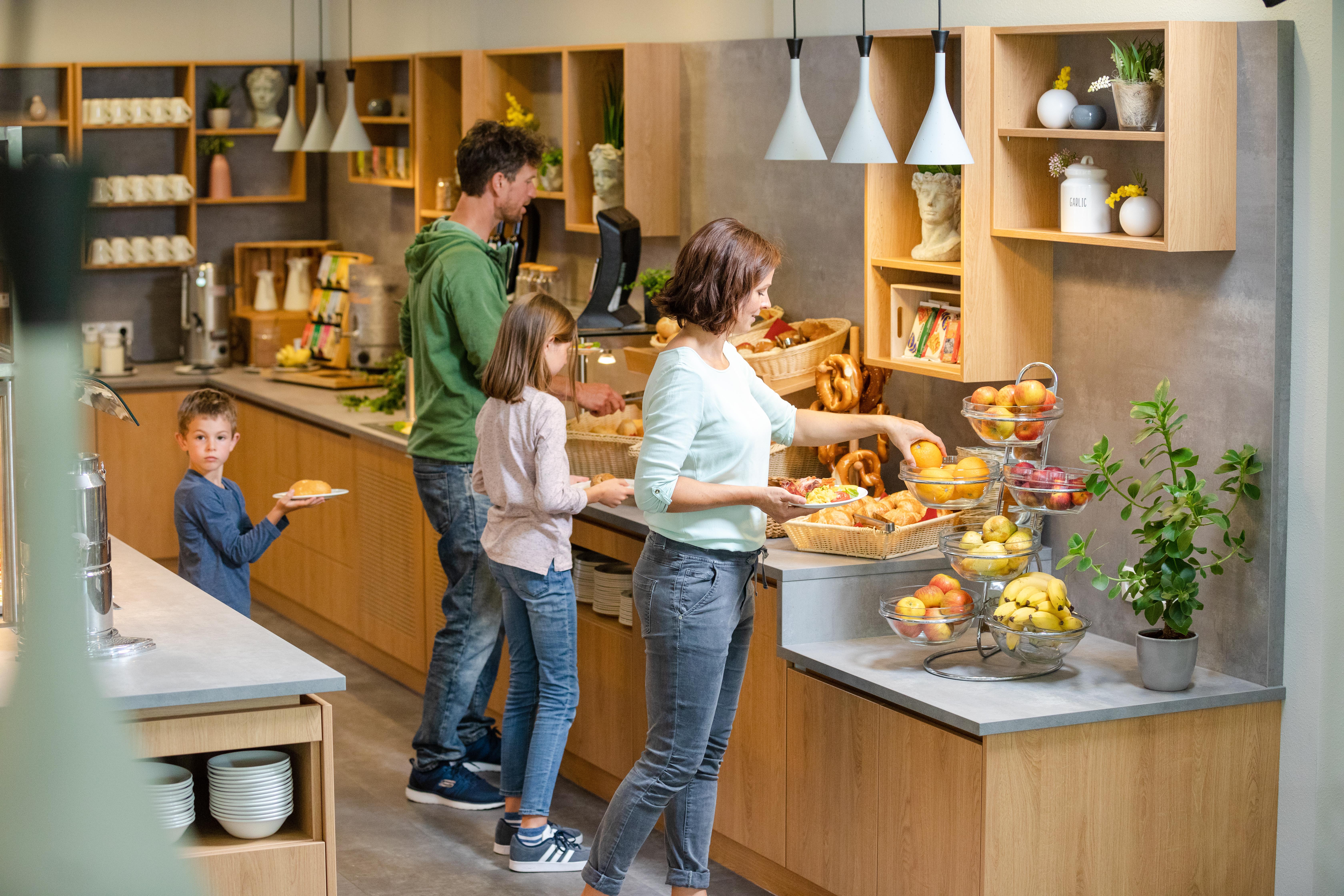 Sie sehen eine Familie am Frühstücksbuffet im JUFA Kempten mit herzhafter oder süßer Auswahl. JUFA Hotels bietet kinderfreundlichen und erlebnisreichen Urlaub für die ganze Familie.