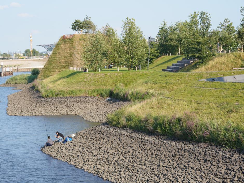 Sie sehen das Ufer und die Grünanlage des Baakenparks im Hamburger Stadtteil Hafencity. JUFA Hotels bietet erlebnisreichen Städtetrip für die ganze Familie und den idealen Platz für Ihr Seminar.