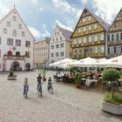 Sie sehen die Stadt Bad Mergentheim mit dem Marktplatz und alten Rathaus im Sommer. JUFA Hotels bietet erholsamen Familienurlaub und einen unvergesslichen Winter- und Wanderurlaub.