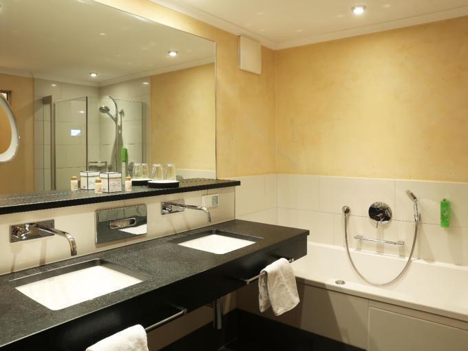 Sie sehen ein Badezimmer im JUFA Alpenhotel Saalbach**** mit Badewanne und Spiegel. JUFA Hotels bietet erholsamen Familienurlaub und einen unvergesslichen Winterurlaub.