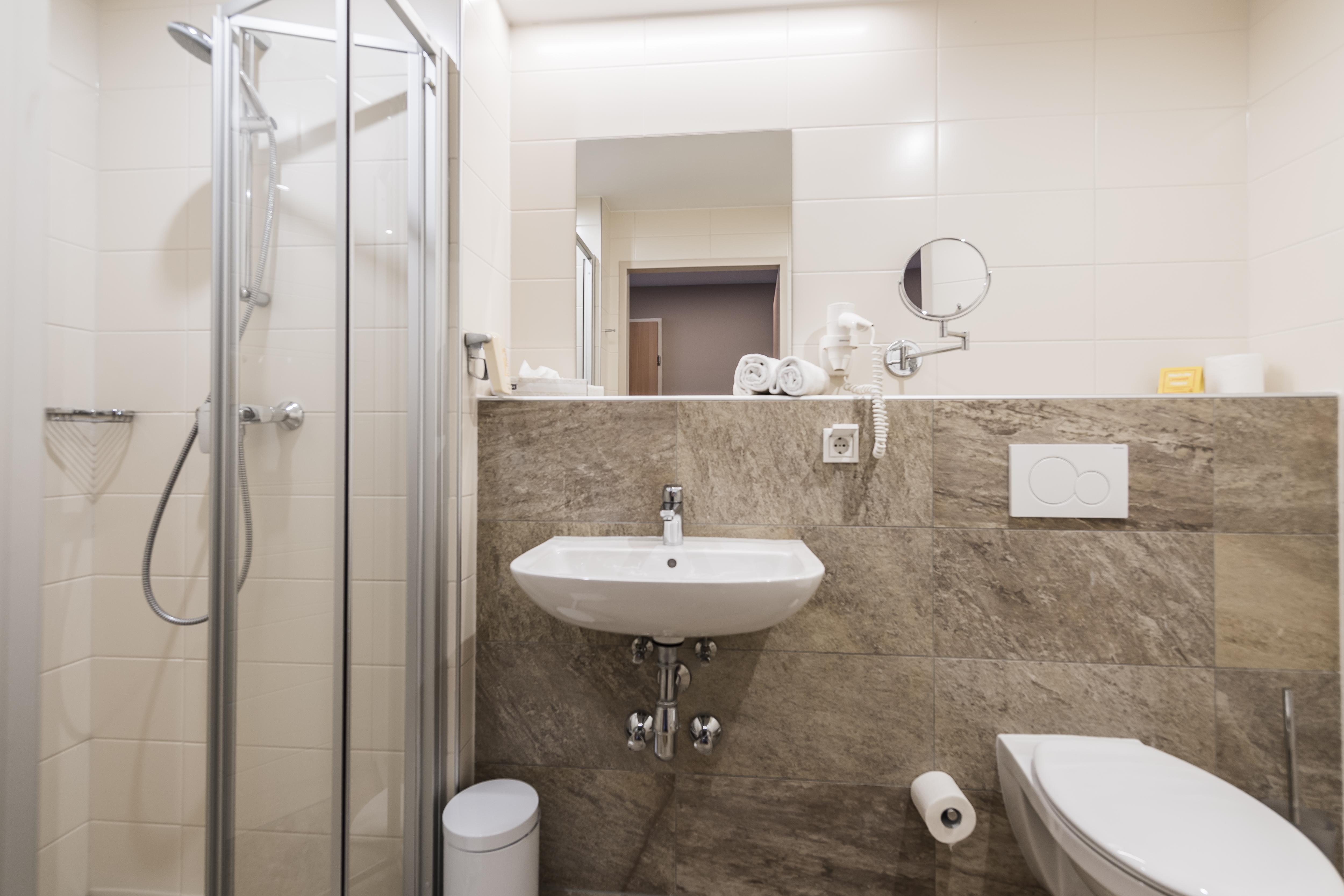 Sie sehen ein Badezimmer im JUFA Hotel Grundlsee*** mit einem Waschbecken. JUFA Hotels bietet erholsamen Familienurlaub und einen unvergesslichen Winter- und Wanderurlaub.
