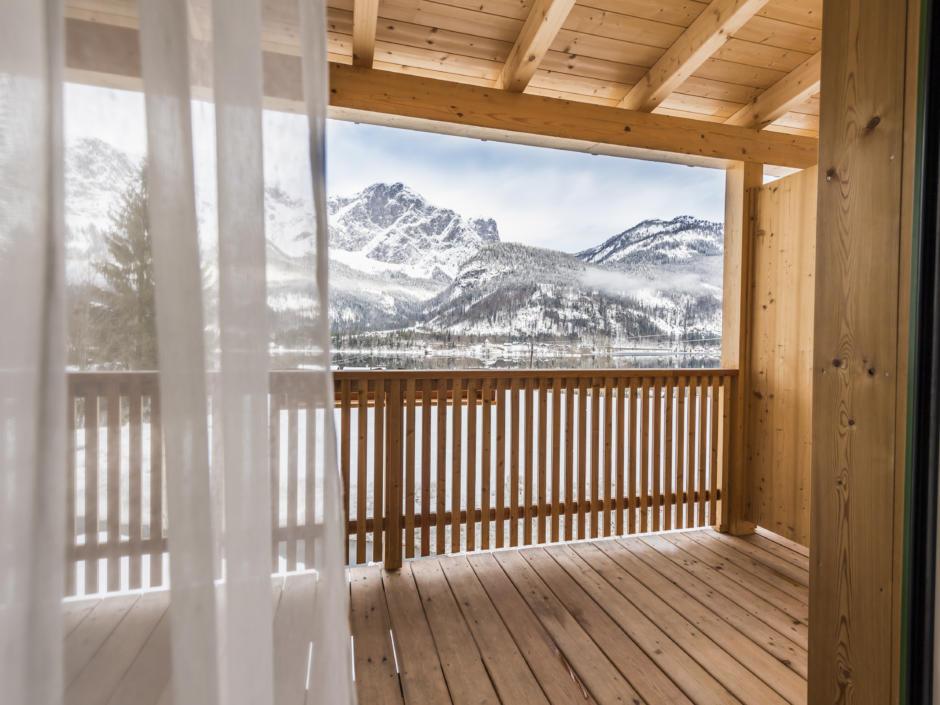 Sie sehen einen Balkon im JUFA Hotel Grundlsee*** mit Bergpanorama im Winter. JUFA Hotels bietet erholsamen Familienurlaub und einen unvergesslichen Winterurlaub.