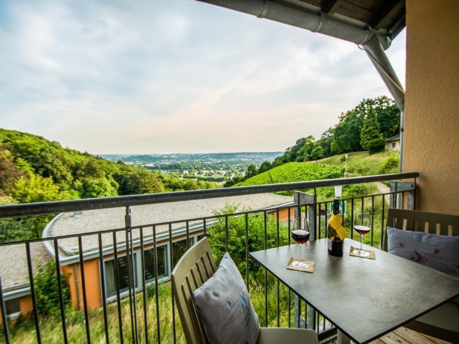 Balkon eines Zimmers im JUFA Hotel Königswinter/Bonn mit Wein und tollem Ausblick. JUFA Hotels bietet erlebnisreichen Städtetrip für die ganze Familie und den idealen Platz für Ihr Seminar.