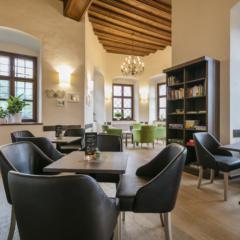 Sie sehen die Bar mit Sitzecke und Regal im JUFA Hotel Schloss Röthelstein/Admont***. Der Ort für märchenhafte Hochzeiten und erfolgreiche und kreative Seminare.