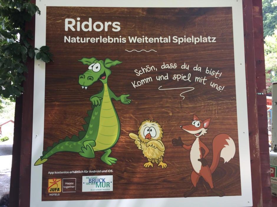Sie sehen die Begrüßungstafel des Ridor Naturerlebnis-Spielplatzes beim JUFA Natur-Hotel Bruck. Der Ort für erholsamen Familienurlaub und einen unvergesslichen Winter- und Wanderurlaub.