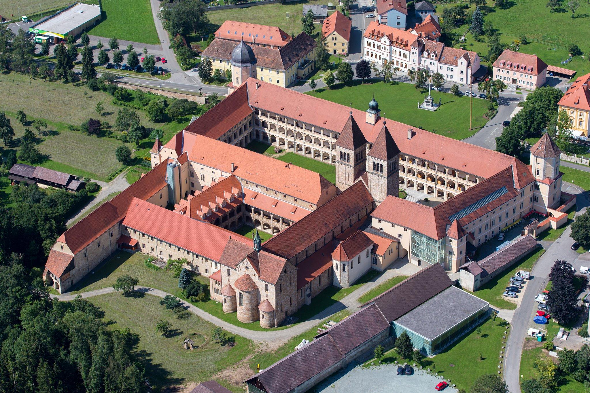 Sie sehen die Benediktinerabtei Seckau aus der Vogelperspektive im Sommer. JUFA Hotels bietet erholsamen Familienurlaub und einen unvergesslichen Winter- und Wanderurlaub.