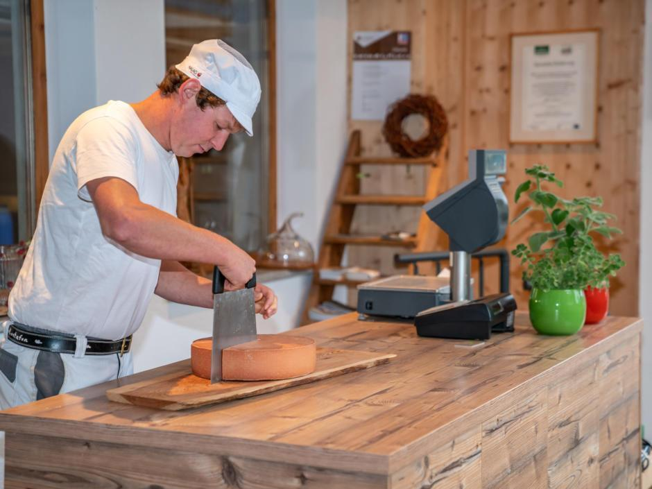 Sie sehen einen Mann bei der Käseherstellung am Bergbauernhof Ganahl in Bartholomäberg. JUFA Hotels bietet kinderfreundlichen und erlebnisreichen Urlaub für die ganze Familie.