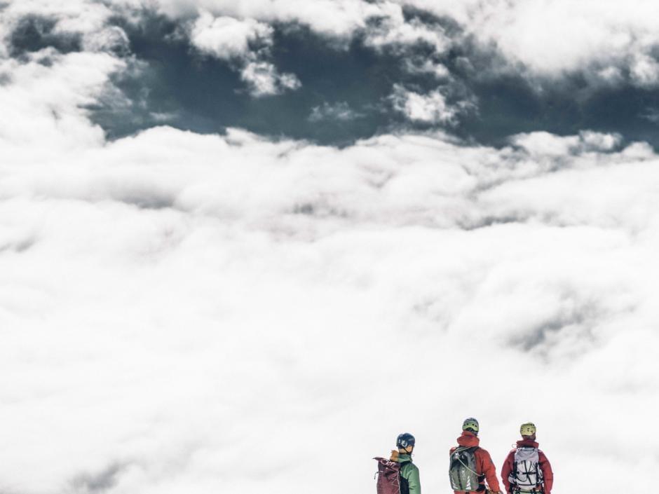 Sie sehen eine Bergsteigergruppe auf dem Gipfel eines Berges im Nationalpark Gesäuse über den Wolken.