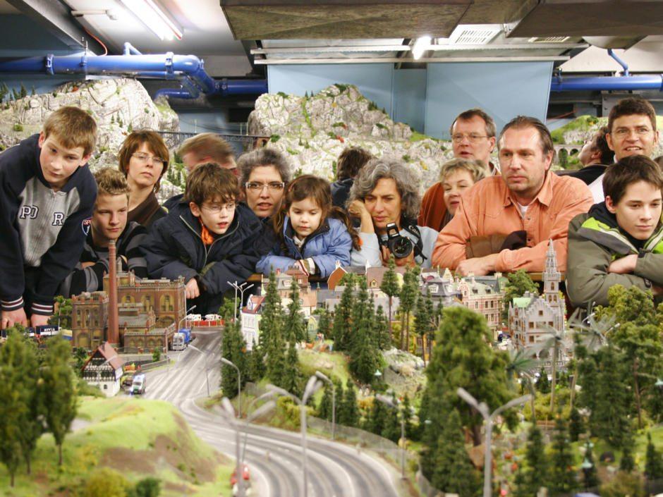 Eine Gruppe von Besuchern bestaunt eine Ministadt im Miniatur Wunderland Hamburg in der Nähe vom JUFA Hotel Hamburg Hafen City. Der Ort für erlebnisreichen Städtetrip für die ganze Familie und der ideale Platz für Ihr Seminar. Ideal als Kindermuseen in Hamburg.
