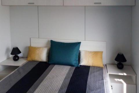 Sie sehen ein Bett in einem Mobile Home am JUFA Vulkan Thermen-Resort mit Kissen. JUFA Hotels bietet erholsamen Thermenspass für die ganze Familie.