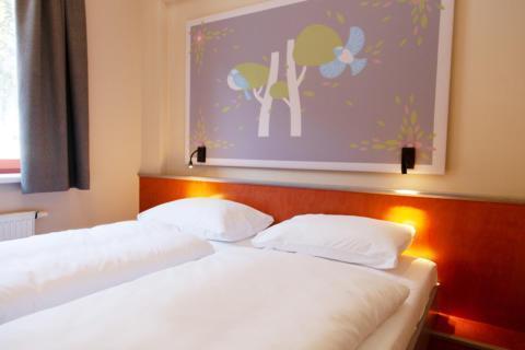 Sie sehen ein Doppelbett vor Wand im Doppelzimmer im JUFA Hotel Mariazell – Sigmundsberg. Der Ort für erholsamen Familienurlaub und einen unvergesslichen Winter- und Wanderurlaub.