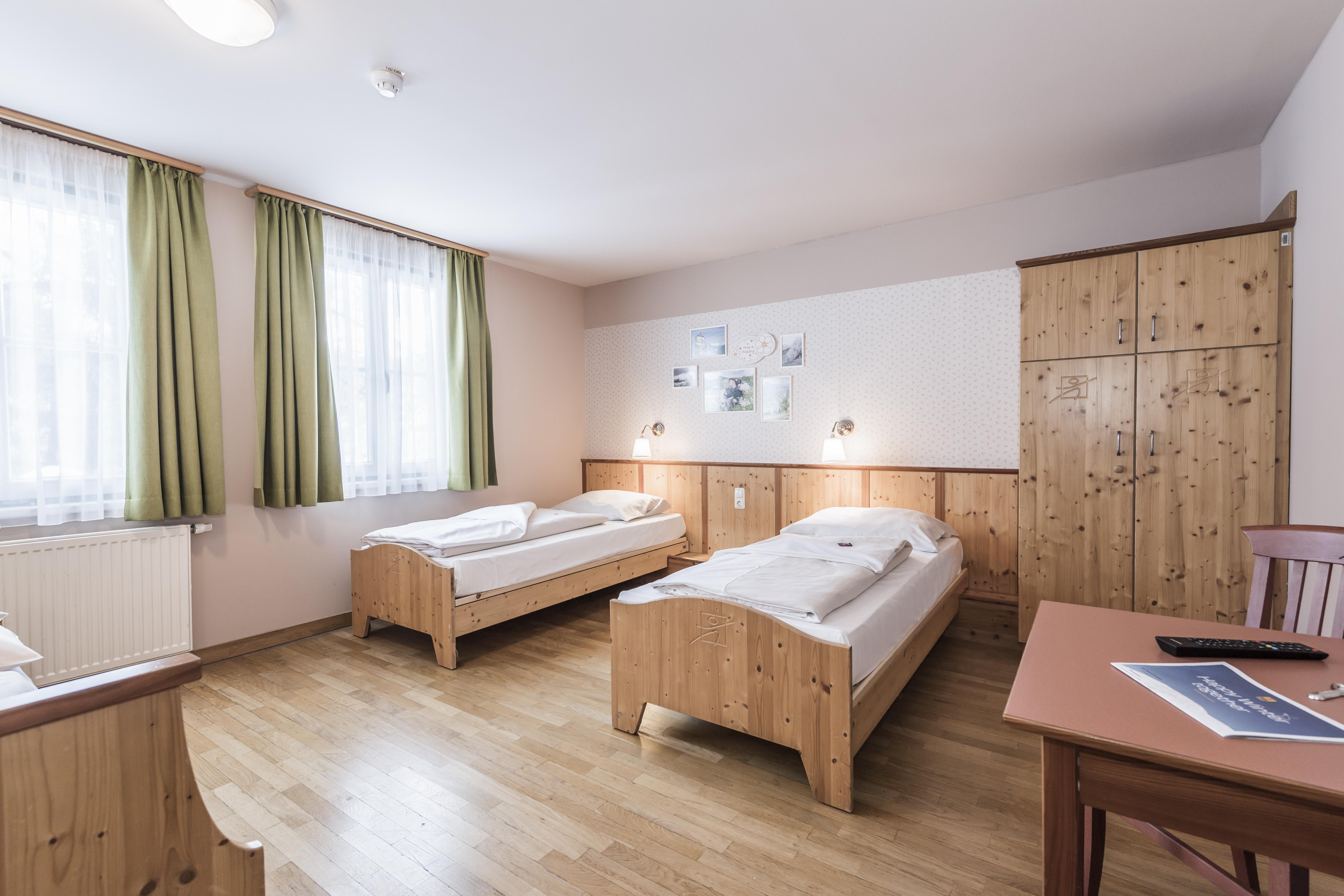 Sie sehen Betten in einem Appartement xxlarge im JUFA Hotel Grundlsee*** mit einem Kleiderschrank. JUFA Hotels bietet erholsamen Familienurlaub und einen unvergesslichen Winter- und Wanderurlaub.