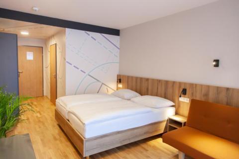 Sie sehen ein Doppelbett im Doppelzimmer/Familienzimmer FF3 im JUFA Hotel Mariazell – Erlaufsee Sport-Resort. Der Ort für erfolgreiches Training in ungezwungener Atmosphäre für Vereine und Teams.