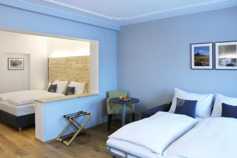 Sie sehen Betten in einem Familienzimmer Typ Family & Friends 4 im JUFA Alpenhotel Saalbach**** mit Sitzgelegenheit. JUFA Hotels bietet erholsamen Familienurlaub und einen unvergesslichen Winterurlaub.