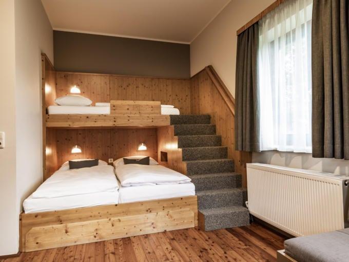 Sie sehen drei Betten in einem Familienzimmer Typ Family and Friends 4 Plus im JUFA Hotel Maria Lankowitz mit Treppe. JUFA Hotels bietet tollen Sommerurlaub an schönen Seen für die ganze Familie.