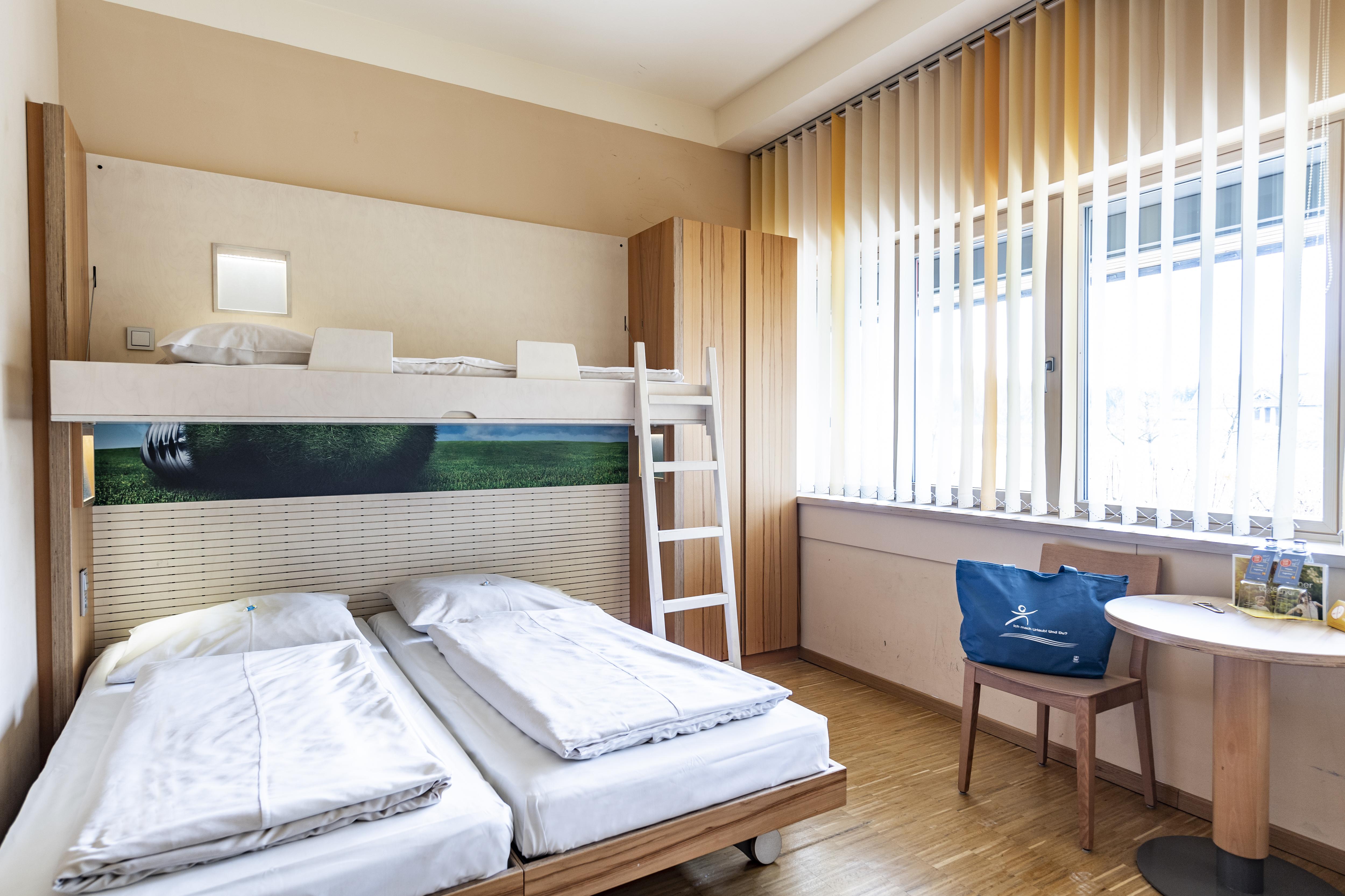Sie sehen Betten in einem Familienzimmer medium Typ Family and Friends 3 im JUFA Hotel Bleiburg/Pliberk – Sport-Resort mit einer Sitzgelegenheit. JUFA Hotels bietet Ihnen den Ort für erfolgreiches Training in ungezwungener Atmosphäre für Vereine und Teams.