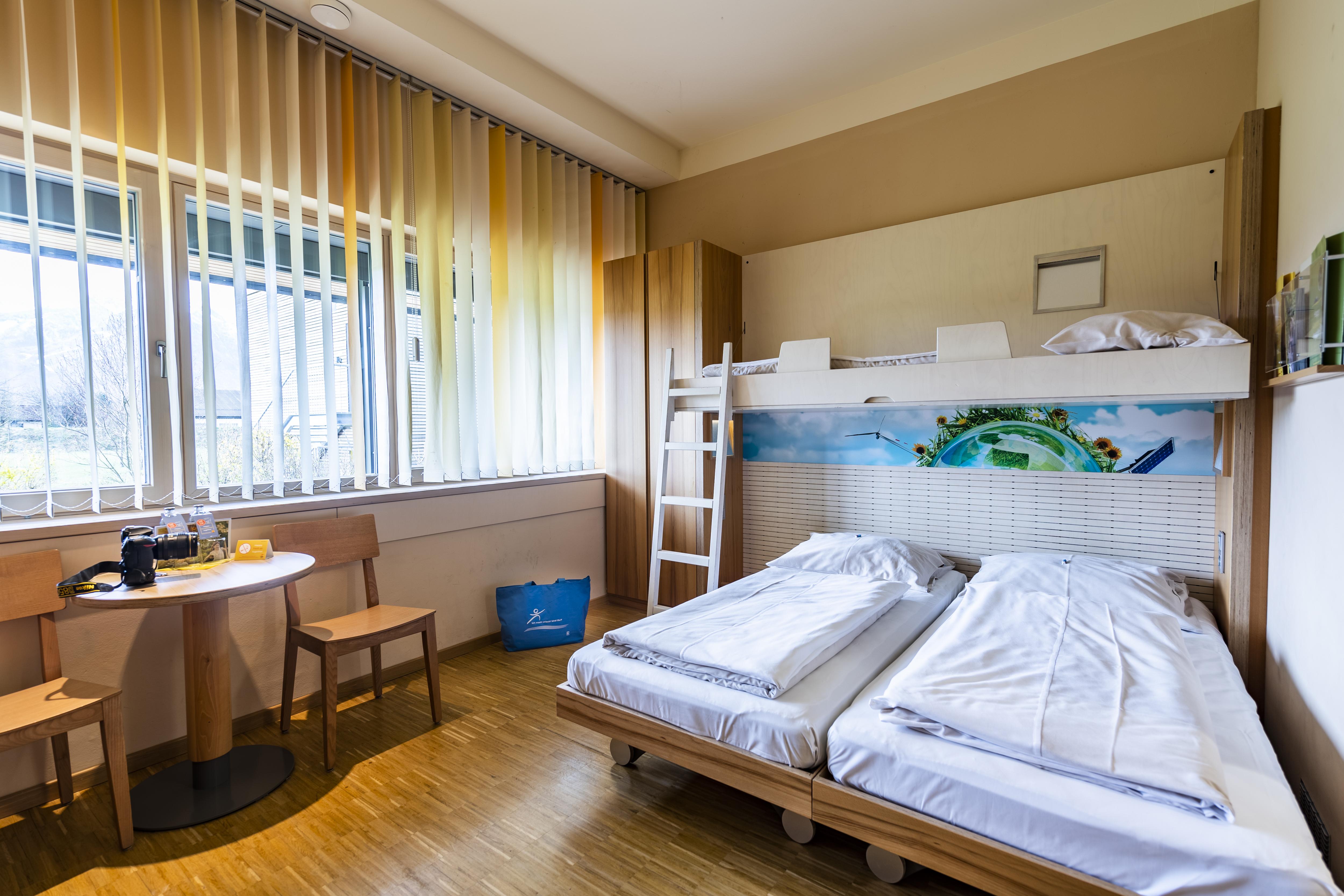 Sie sehen Betten in einem Familienzimmer medium Typ Family and Friends 3 im JUFA Hotel Bleiburg/Pliberk – Sport-Resort mit einem Tisch. JUFA Hotels bietet Ihnen den Ort für erfolgreiches Training in ungezwungener Atmosphäre für Vereine und Teams.