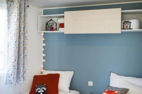 Sie sehen Betten in einem Mobile Home beim JUFA Vulkan Thermen-Resort mit Kinderspielzeug. JUFA Hotels bietet erholsamen Thermenspass für die ganze Familie.