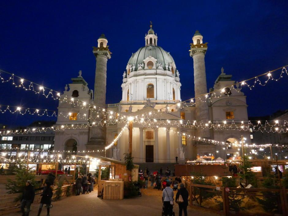 Sie sehen den Bio-Adventmarkt am Karlsplatz in Wien mit der Karlskirche. JUFA Hotels bietet erholsamen Familienurlaub und einen unvergesslichen Winterurlaub.