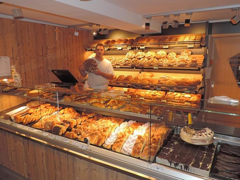 Sie sehen den Verkaufsraum mit einem Verkäufer der Biobäckerei Oesterlein in Kronach, die das JUFA Hotel Kronach – Festung Rosenberg*** mit Brot und Gebäck beliefert. JUFA Hotels bietet kinderfreundlichen und erlebnisreichen Urlaub für die ganze Familie.