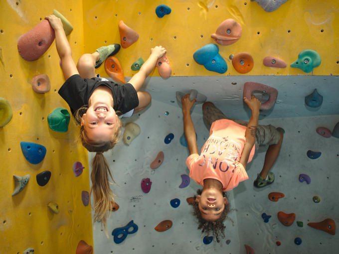 Sie sehen Kids beim Bouldern im City Adventure Center in Graz. JUFA Hotels bietet tollen Urlaub mit viel Abenteuer und Spass für die ganze Familie.