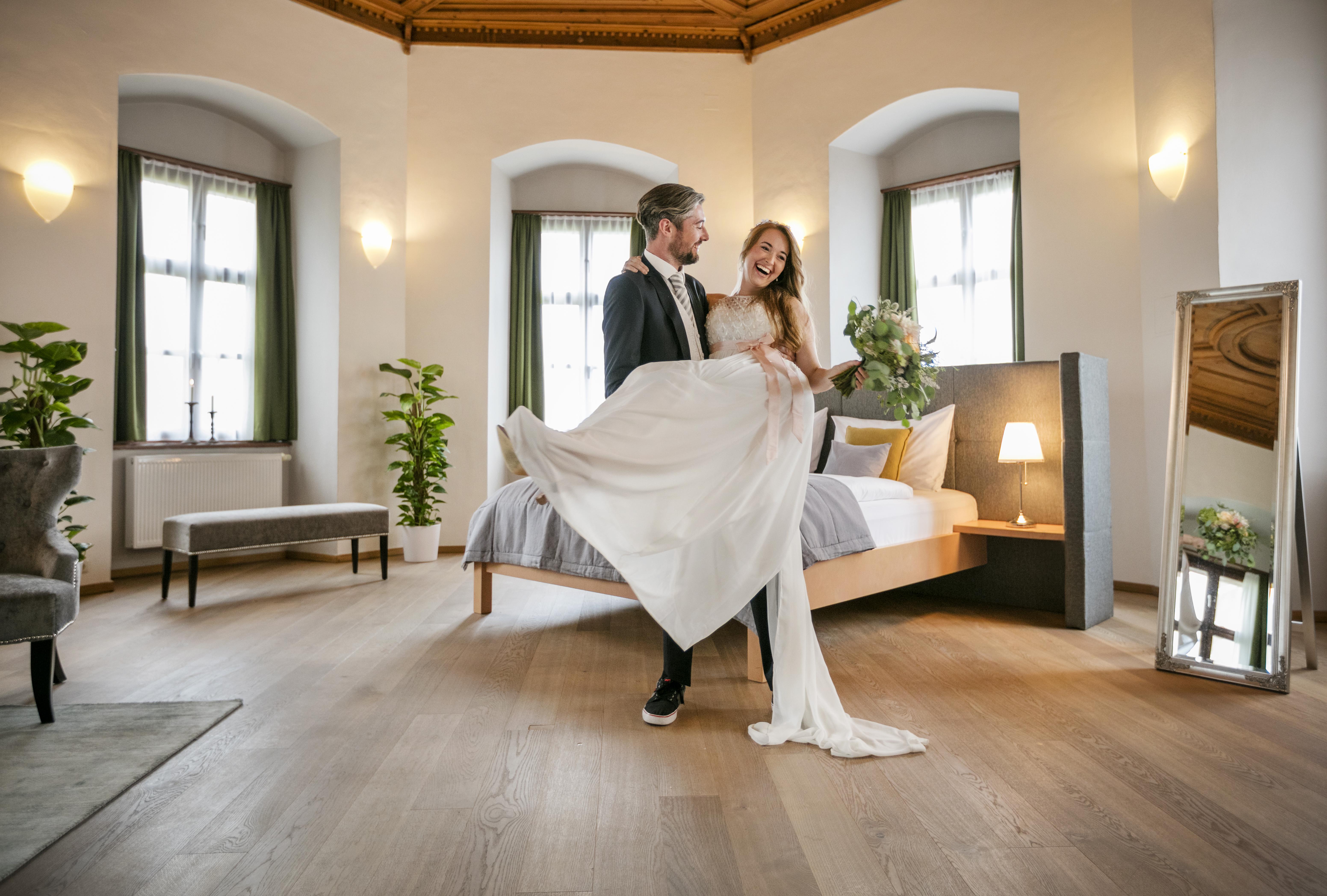 Sie sehen ein Brautpaar im Hochzeitszimmer des JUFA Hotel Schloss Röthelstein/Admont***. Der Ort für märchenhafte Hochzeiten und erfolgreiche und kreative Seminare.