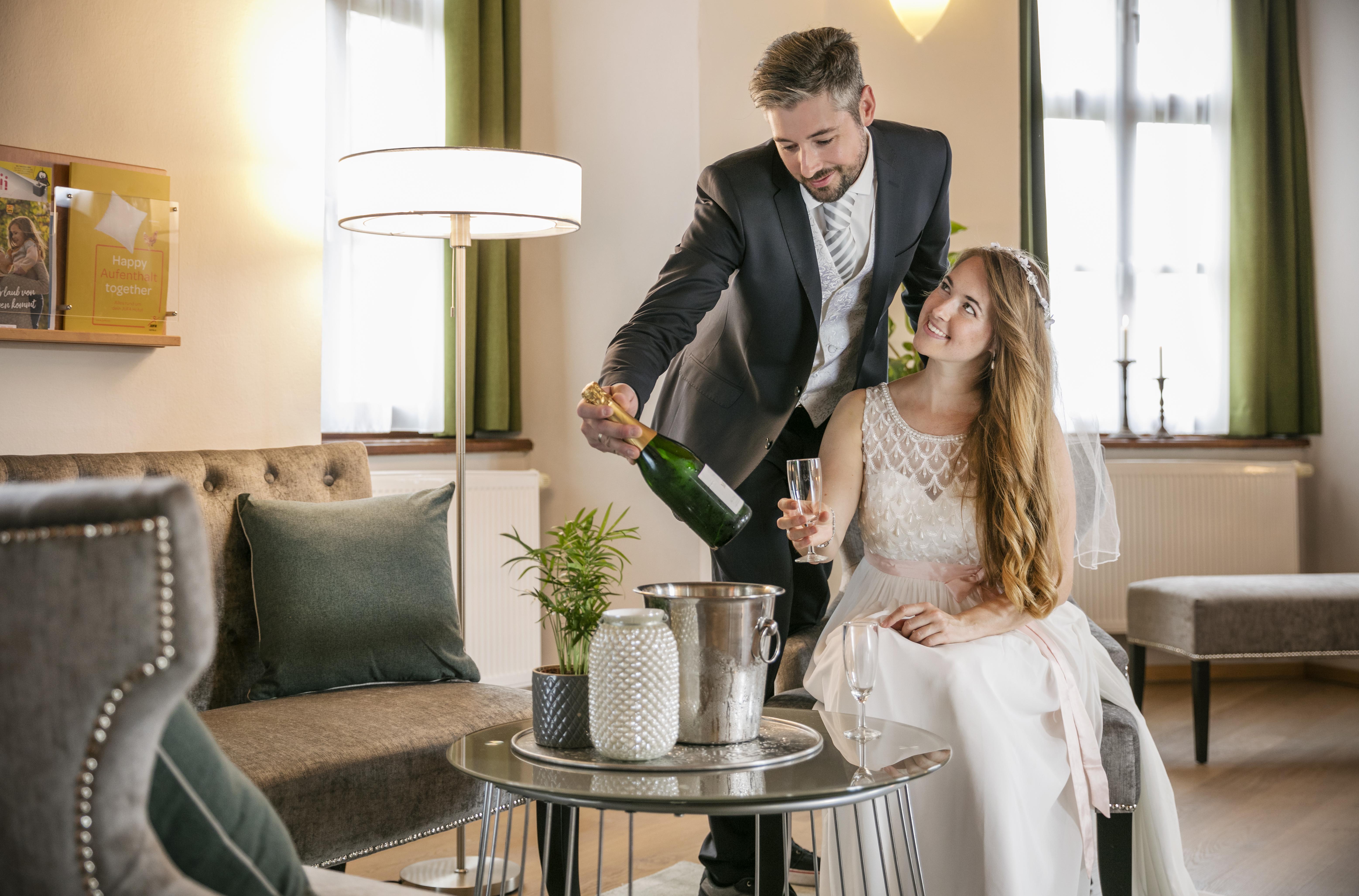 Sie sehen ein Brautpaar imit Sektflasche im Hochzeitszimmer des JUFA Hotel Schloss Röthelstein/Admont***. Der Ort für märchenhafte Hochzeiten und erfolgreiche und kreative Seminare.