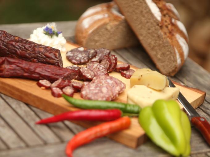 Sie sehen eine Brettljause mit Wurst und Käse. JUFA Hotels bietet erholsamen Familienurlaub und einen unvergesslichen Winter- und Wanderurlaub.