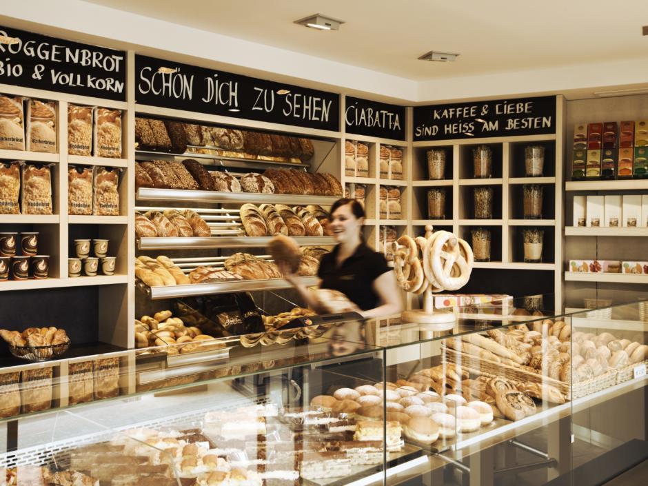 Sie sehen das Brotsortiment und eine Verkäuferin in der Brotbar Cafe-Bäckerei in Kaindorf in der Steiermark. JUFA Hotels bietet erholsamen Familienurlaub und einen unvergesslichen Winter- und Wanderurlaub.