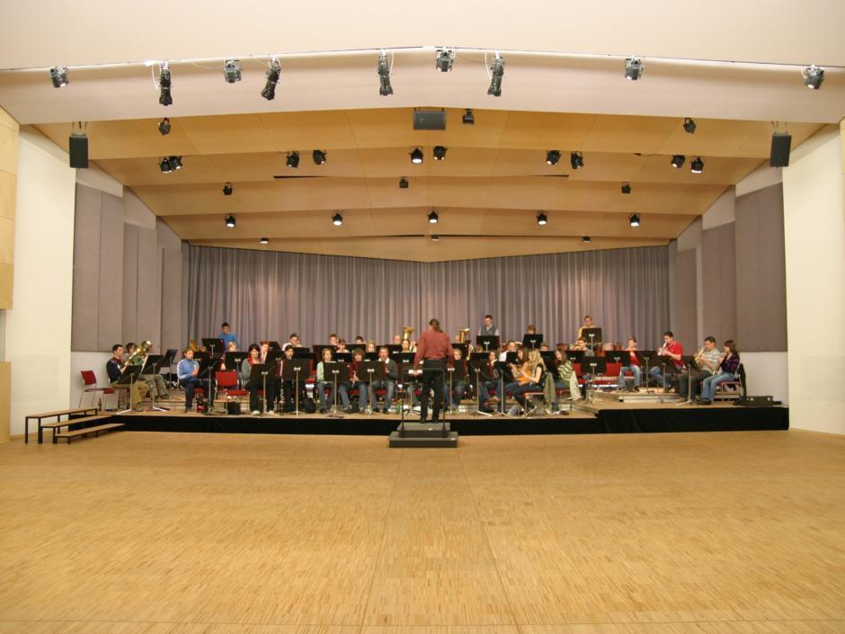 Sie sehen die Bühne des Musikzentrums Knappenberg mit Orchester. JUFA Hotels bietet den idealen Platz zum Musizieren und Singen in der Gemeinschaft in abwechslungsreichen Regionen.