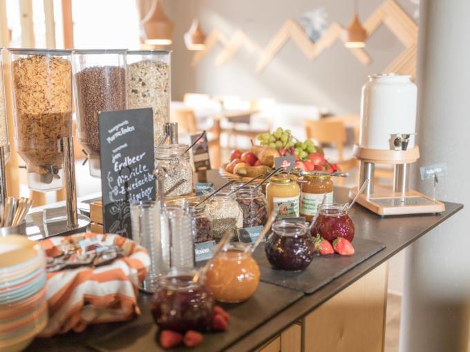 Sie sehen Marmeladen und Müsli am Frühstückbuffet im JUFA Hotel Montafon. Der Ort für erholsamen Familienurlaub und einen unvergesslichen Winter- und Wanderurlaub.