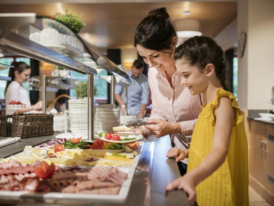 Sie sehen Personen beim Frühstücksbuffet im JUFA Hotel Sigmundsberg. Der Ort für erholsamen Familienurlaub und einen unvergesslichen Winter- und Wanderurlaub.