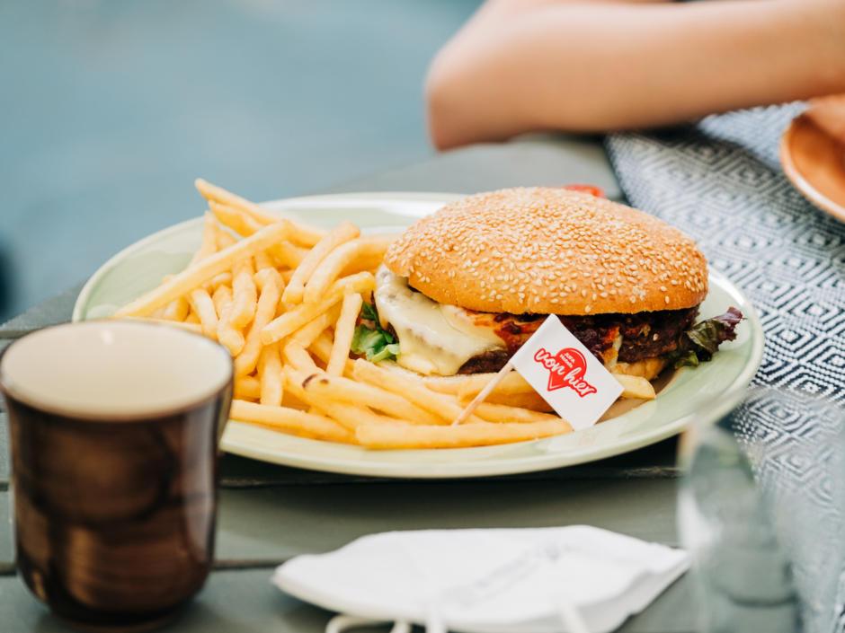 Sie sehen ein leckeres Burger-Teller und Getränk im JUFA Hotel Lipizzanerheimat. Der Ort für erlebnisreichen Natururlaub für die ganze Familie.