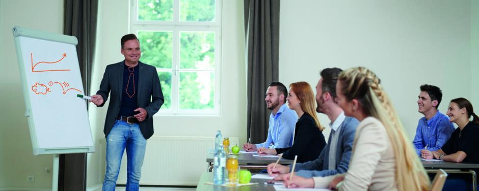 Sie sehen einen Vortrag in einem gut ausgestatteten Seminarraum im JUFA Hotel Stift Gurk. Der Ort für erfolgreiche und kreative Seminare in abwechslungsreichen Regionen.